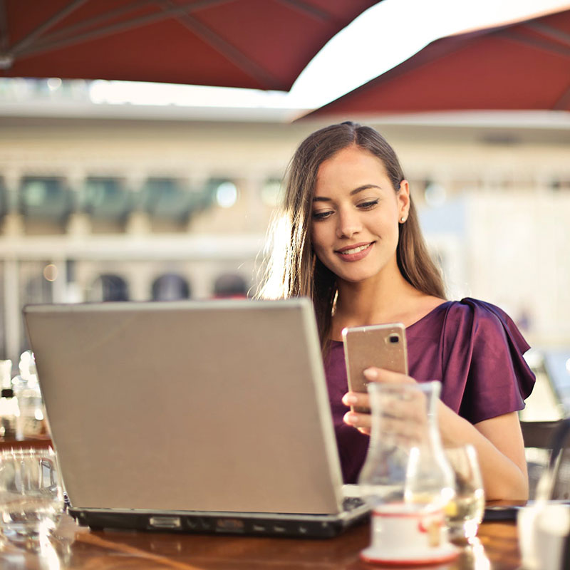 Women sitting at table in front of laptop holding smart phone