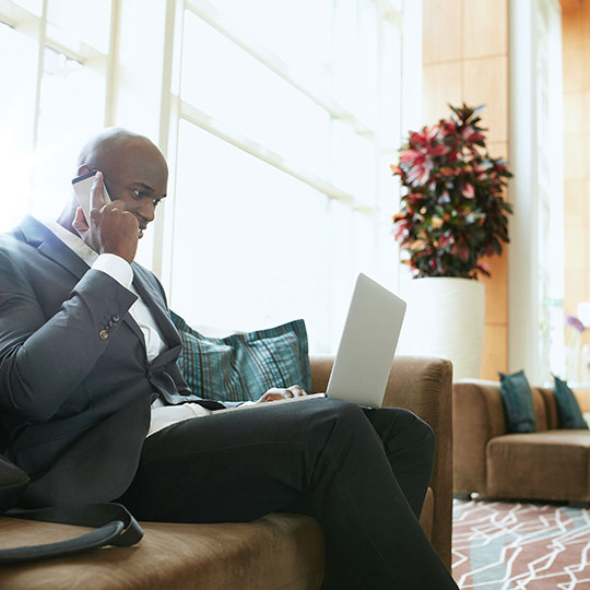 Man sitting and talking on phone with laptop on his legs