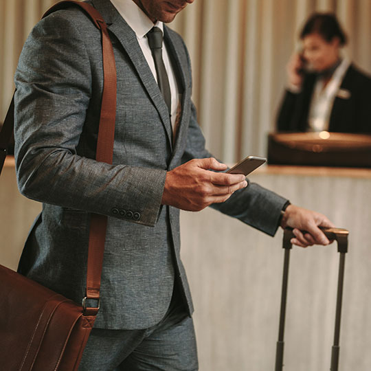 Man in suit holding smart phone and luggage